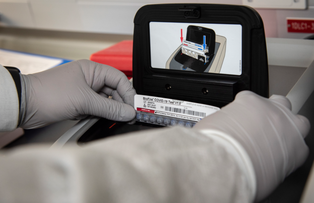 Staff Sgt. Nathan Harris, 96th Medical Group medical laboratory technician, places a patient sample in a molecular diagnostic analyzer used to test for COVID-19 May 1 at Eglin Air Force Base, Fla. It takes approximately 70 minutes to process each panel. (U.S. Air Force photo/Ilka Cole)
