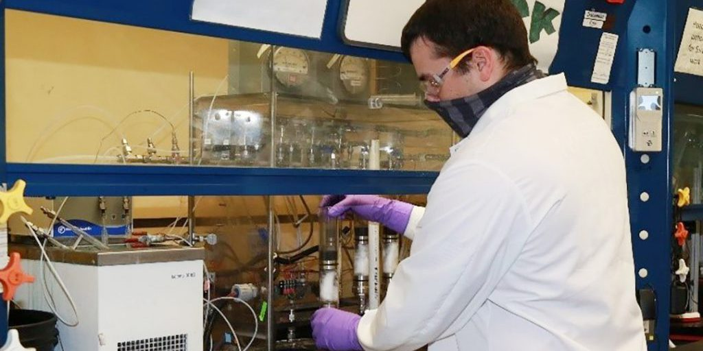 Aaron Salgado, a DEVCOM CBC chemist, places a tube containing a layer of carbon from the second source into a testing system that will analyze the time it would take a chemical agent to break through it (U.S. Army).